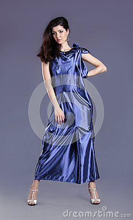 Young brunette lady in blue dress posing
