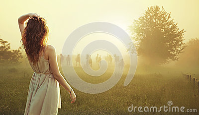 Young brunette lady watching herd of horses Stock Photo