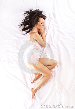A young brunette is lying on a white silk bed