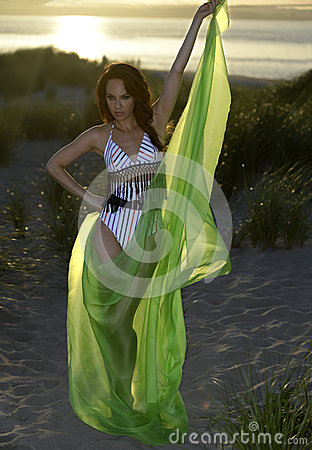 Young brunette model posing in design  bikini and holding green floating beach cover up on sunset time