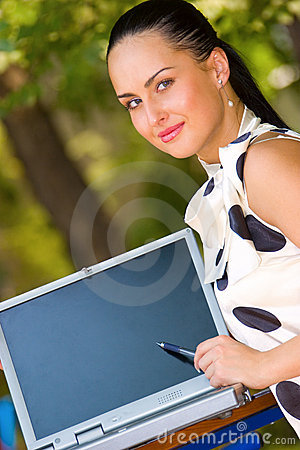 Young brunette pointing with pen on laptop screen