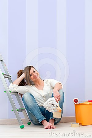Young brunette sitting on floor after painting.