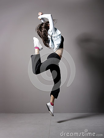 A young brunette woman dancing in sporty clothes