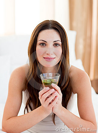 Young brunette woman drinking tea sitting on bed