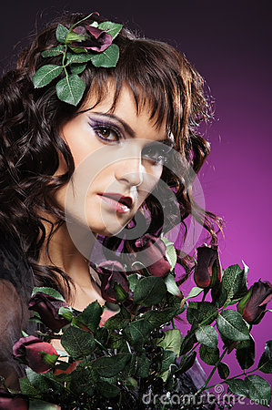 A young brunette woman in flowers and beautiful makeup