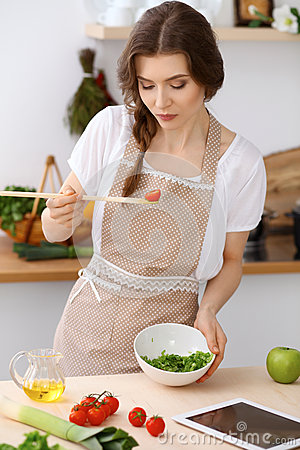 Free Young Brunette Woman Is Cooking And Tasting Fresh Salad In The Kitchen. Housewife Holding Wooden Spoon In Her Hand Stock Photo - 93269830