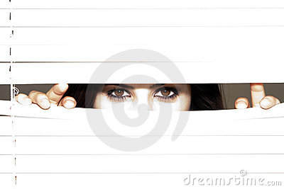 Young Brunette Woman Looking Through The Blinds