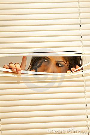 Young Brunette Woman Looking Through Window Blinds