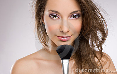 Young brunette woman with makeup brush.