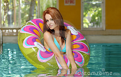Young brunette woman playing in a swimming pool