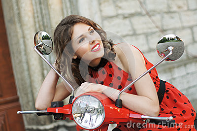 A young brunette woman in a red dress on a scooter