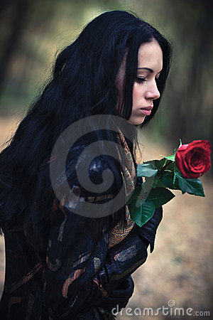 Young brunette woman with red rose portrait