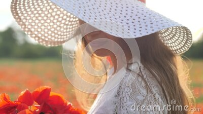 Young brunette woman in white dress and big hat stands in the middle of the field of poppies. Charming lady with stock video footage