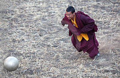 Young buddhist monk playing soccer Editorial Stock Photo