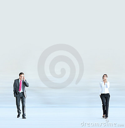 A young business couple walking with phones