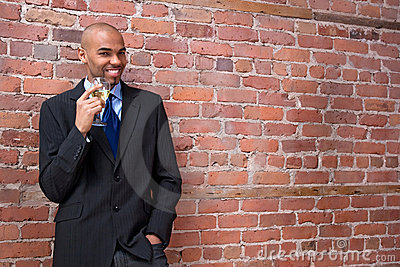 Young business man drinking wine and smiling