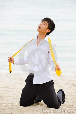 Young business man on his knees at the beach