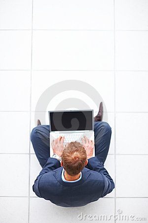 Young business man sitting on floor using  laptop