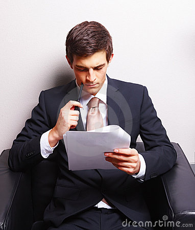 Young business man sitting and reading paper