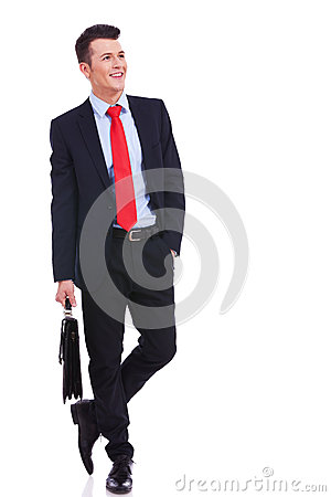Young business man with suitcase looking to side
