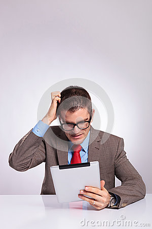 Young business man with tablet scratches his head