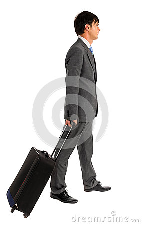 Young business man walking with his trolley bag