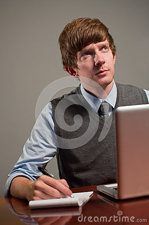 Young Business Man Writing on Notepad with Laptop