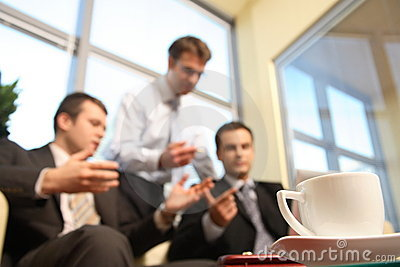 Young business men talking in an office -blur
