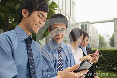 Young business people checking their cell phones and smiling