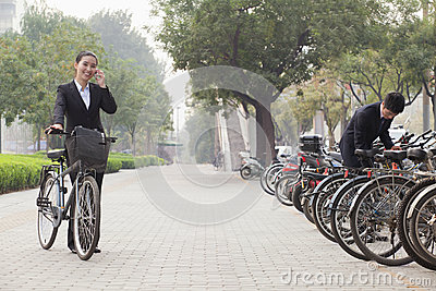 Young business people parking their bicycles and talking on the phone on the sidewalk in Beijing, China