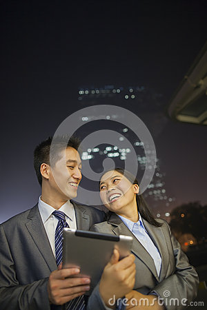 Young business people smiling and holding digital tablet, night and outdoors
