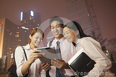 Young business people smiling and working outdoors at night