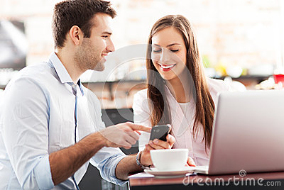 Business people using laptop at cafe