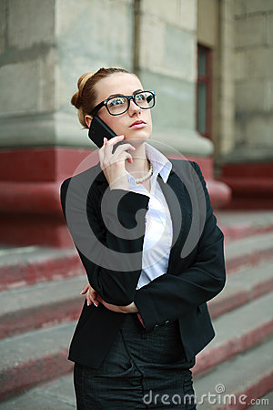 Young business woman in black suit and glasses talking on phone