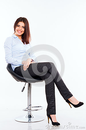 Young business woman in blue shirt sitting on the modern chair against ...