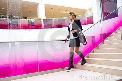 Young business woman coming down the stairs