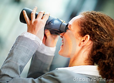 Young business woman looking through binoculars