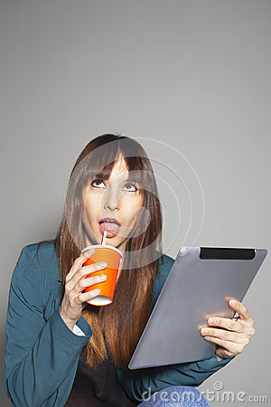 Young business woman looking up and drinking refreshment with digital tablet