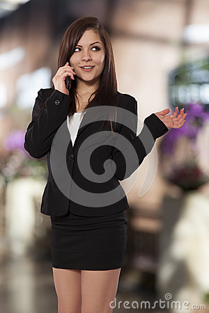 Beautiful young woman in form fitting business clothes has a phone