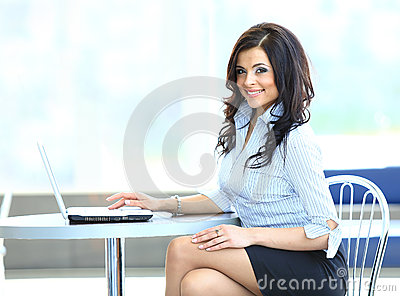 Young business woman using laptop at work desk