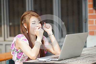 Young business woman working on her laptop at outdoors cafe, She