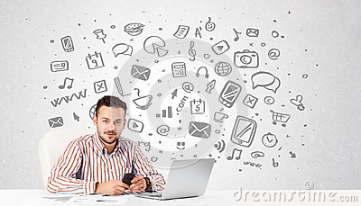 Young businessman with all kind of hand-drawn media icons in bac