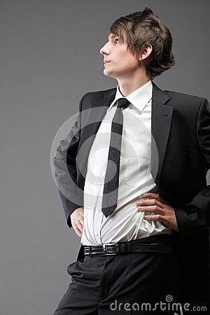 Young businessman black suit casual tie on gray background