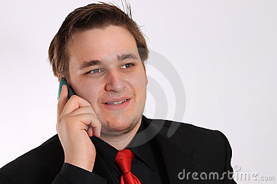 Young businessman in black talking on cellphone