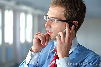 Young businessman in blue shirt talks over mobile