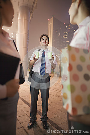 Young businessman bringing coffees for two women at night outdoors