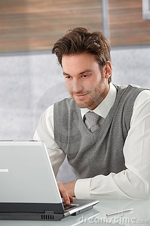 Young businessman browsing internet smiling Stock Photo