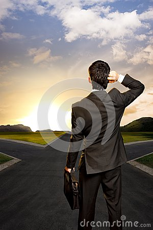 Young businessman in front of a crossroad