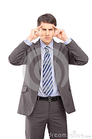 A young businessman holding his head in pain as a result of a he