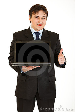 Young businessman holding laptop with blank screen